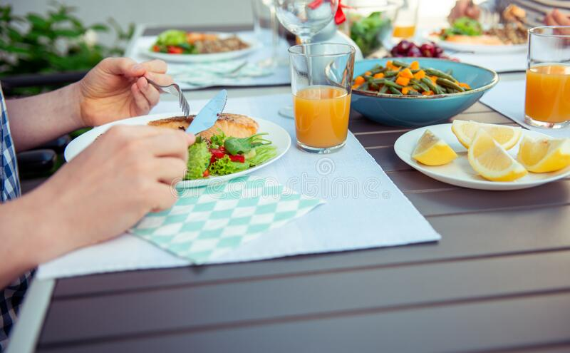 Close up photo of hands man eating salad, quinoa and fish on terrace royalty free stock photography