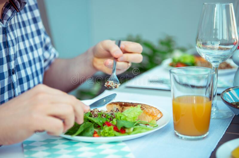 Close up photo of hands man eating salad, quinoa and fish on terrace stock photo