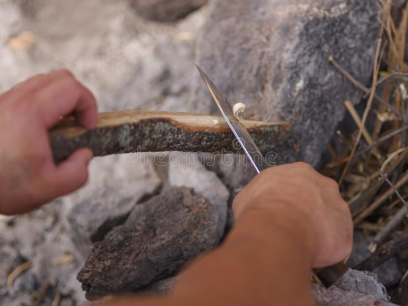 Boys hands start fire with magnesium fire steel, fire striker. royalty free stock photography