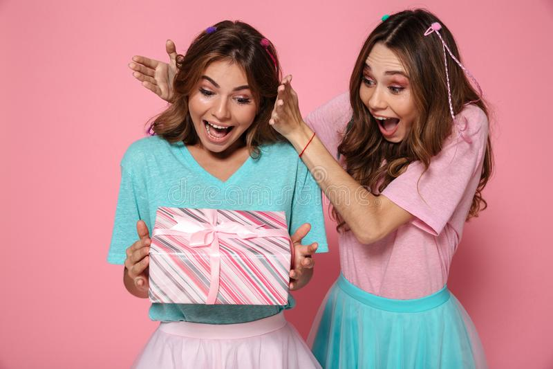 Close-up photo of happy brunette woman giving gift box to her fr royalty free stock image