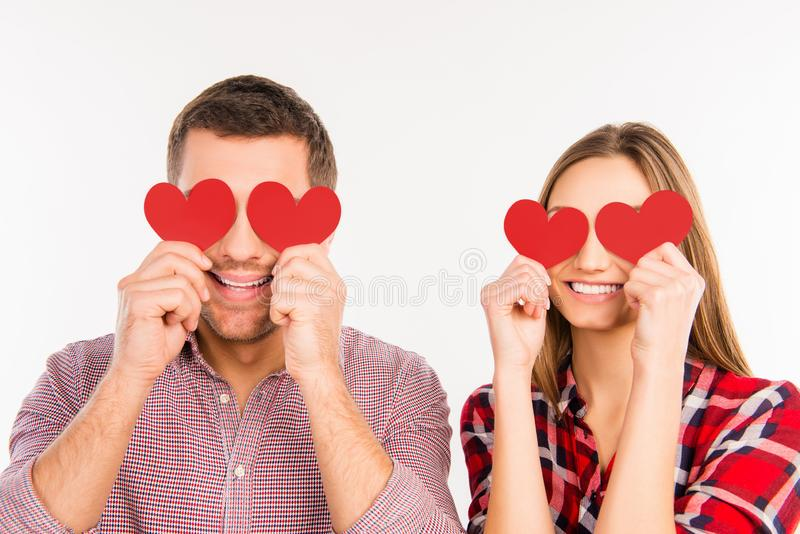 Close up photo of happy couple in love hiding eyes behind paper hearts stock photo
