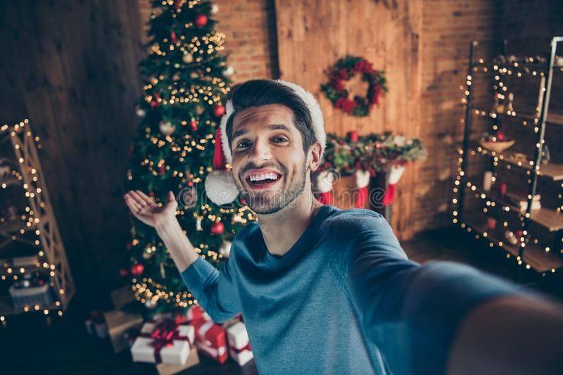 Close up photo of happy joy guy wear santa claus hat make selfie hold hand invite to his x-mas party celebration in royalty free stock images