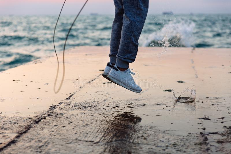 Close-up photo of jumping sportsman with skipping rope, near the sea. Close-up photo of jumping male in sportswear with skipping rope, practice on pier, near the stock photo