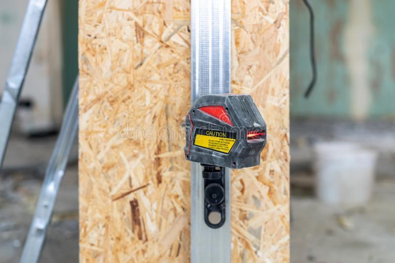 Close up photo of laser level with a red beam stand against room with oriented strand board panel royalty free stock images