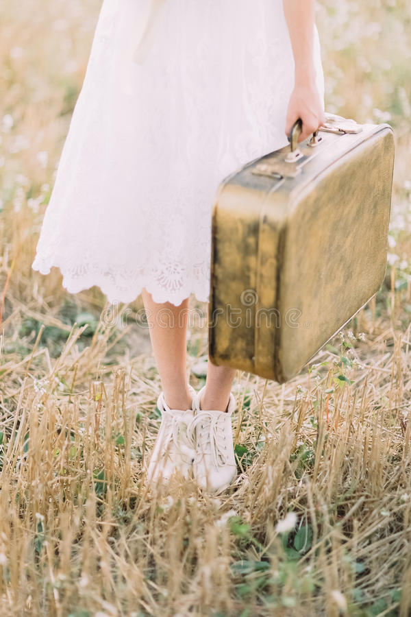 The close-up photo of the legs of the bride dressed in the knee-length dress and carrying the vintage suitcase in the stock photo