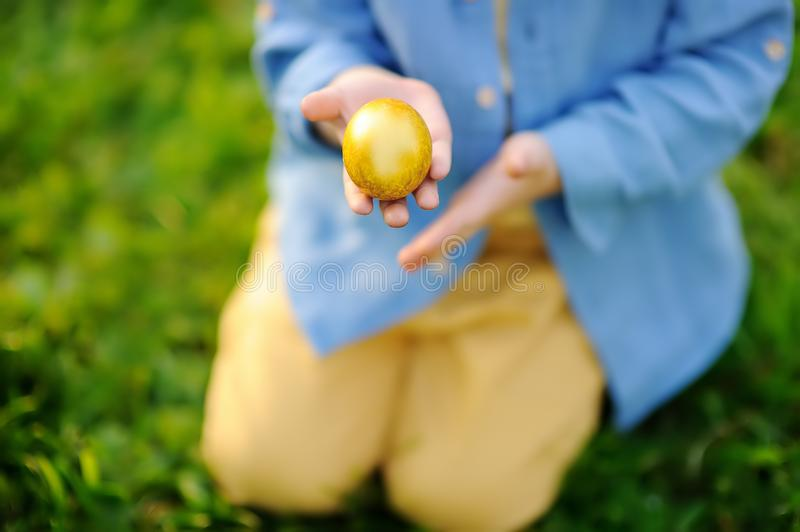 Close-up photo of little boy hunting for easter egg in spring park on Easter day. Cute little child celebrating feast outdoors royalty free stock image