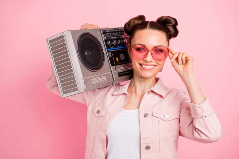 Close up photo of lovely youth holding boom box touching her specs wearing pastel color jacket isolated over pink. Close up photo of lovely youth holding boom royalty free stock photo