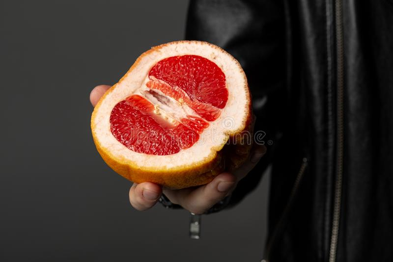 Close up photo of man in leather jacket that holding grapefruit in his hand royalty free stock photo