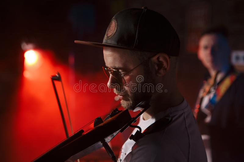 Close-up photo of man playing electric violin royalty free stock photography