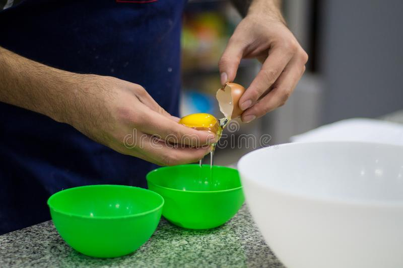 Photo of a man separating eggs. Close up photo of a man separating eggs, cooking, kitchen, bowl, green, yolk, white, chef, handmade royalty free stock images