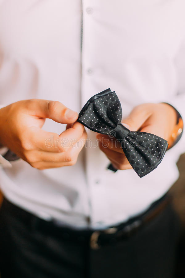 Close-up photo of man in tux holding his bowtie, two hands, no jacket stock image