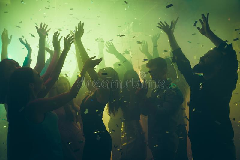 Close up photo of many party people dancing clubbing green lights confetti flying everywhere nightclub hands raised up. Close up photo of many party people stock photos