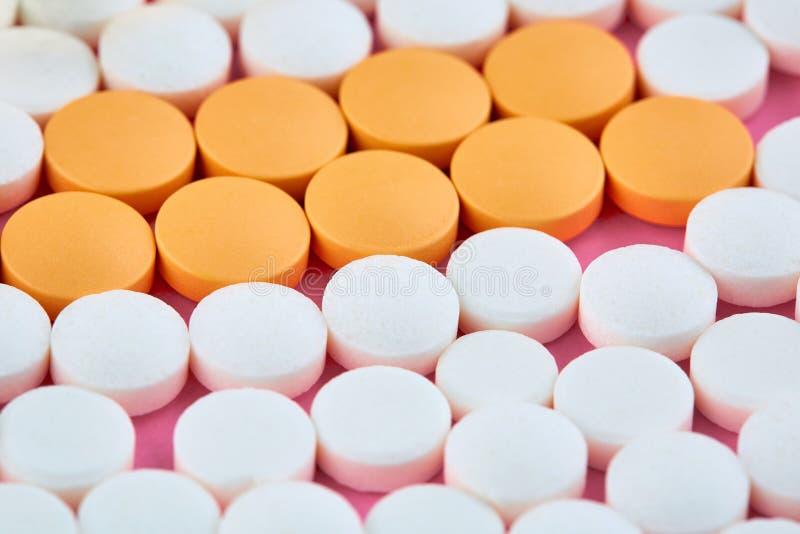 Close up photo of many white and orange pills royalty free stock photo