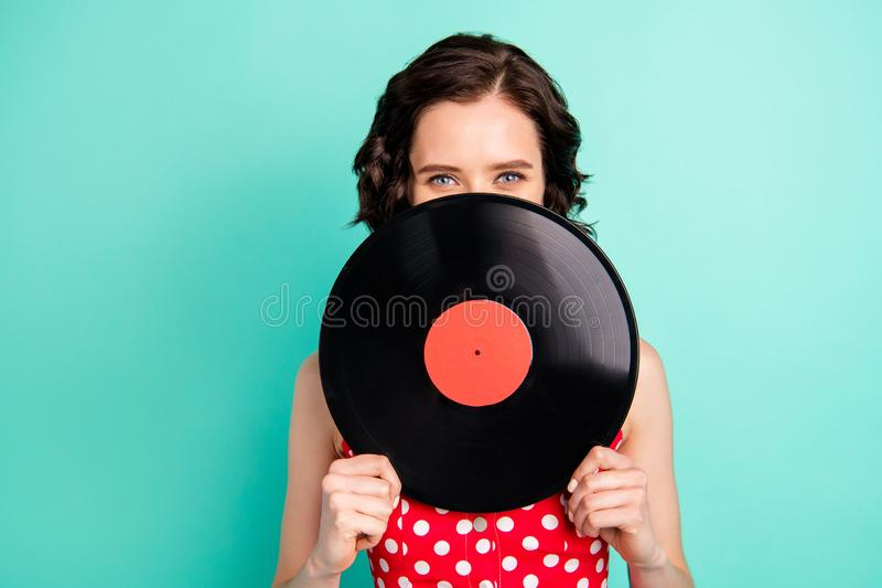 Close up photo of marvelous wonderful charming attractive girlfriend thinking she is small enough to hide behind vinyl. Close up photo of marvelous wonderful royalty free stock photos