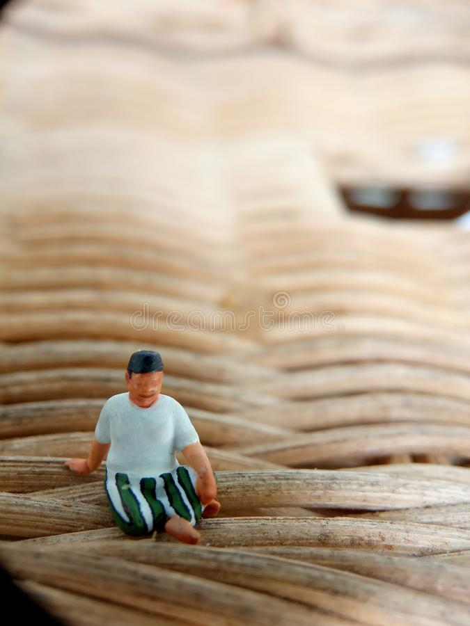 Close Up Photo Mini figure toy Indonesian old man using sarung, kopiah and white shirt, sit at rattan mat, with copy or negative s stock image