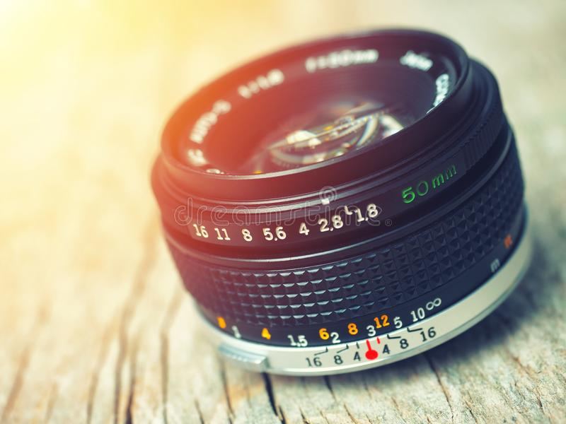 Close up photo of old camera lens over wooden table. Image is retro filtered. selective focus, lens flare stock photo