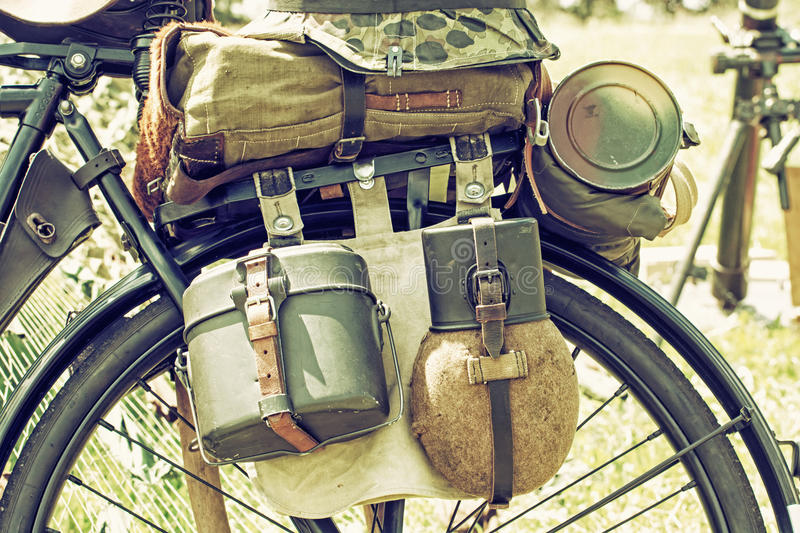 Close up photo of old military bicycle with equipment, retro photo filter. Close up photo of old military bicycle with equipment. Backpack and containers for stock image