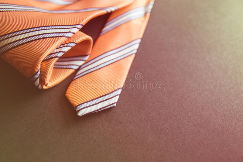 Close - up photo orange men`s tie. Copy space for holiday card or banner on black background.  royalty free stock photo