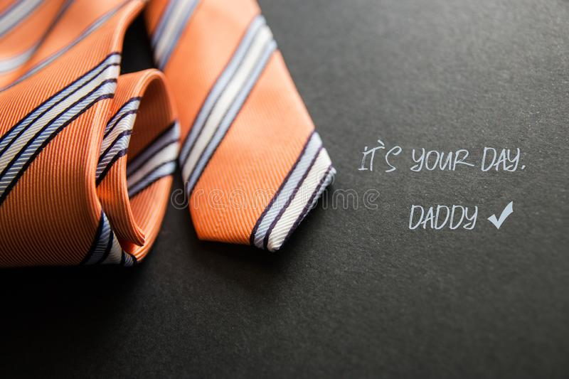Close - up photo orange men`s tie. Text for holiday card or banner on black background stock photos