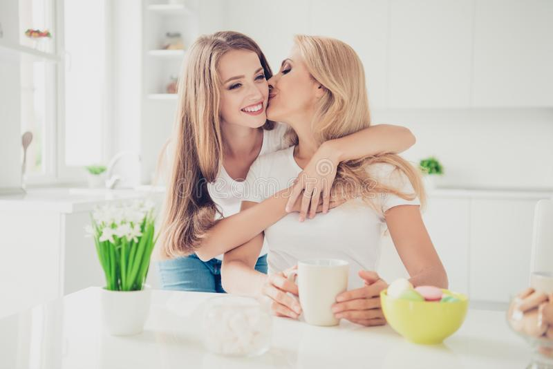 Close up photo piggy-back two people mum and teen daughter drink tea coffee family moment lovely lean on mommy woman royalty free stock photo