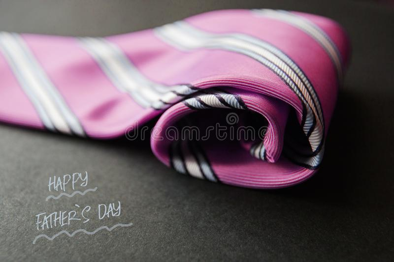 Close - up photo pink men`s tie. Text for holiday card or banner on black background.  royalty free stock photos