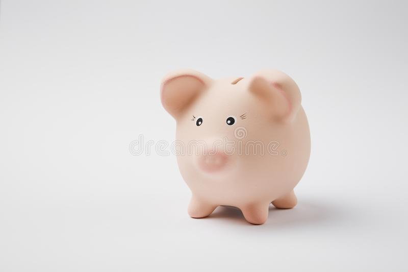 Close up photo of pink rose piggy money bank on white wall background. Money accumulation, investment, banking royalty free stock images
