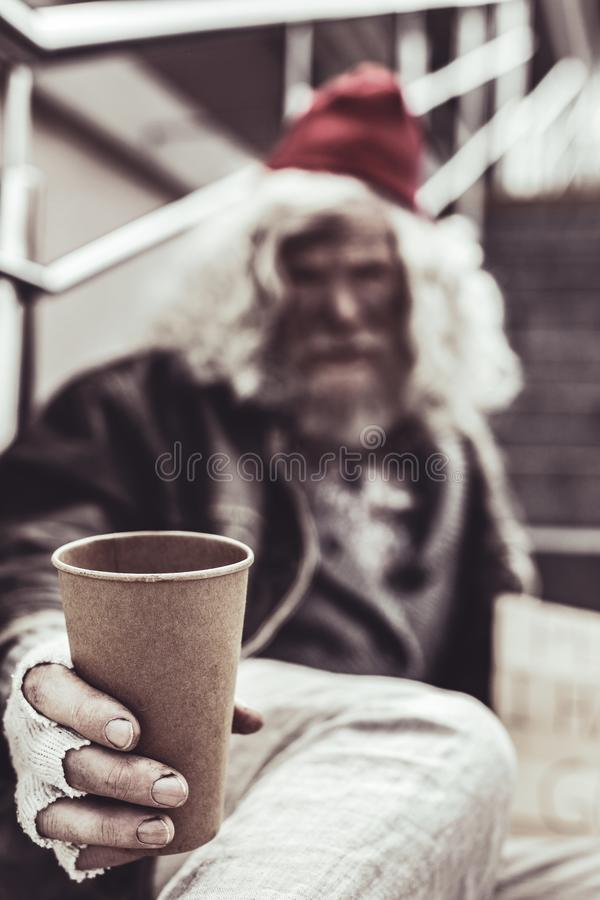 Close up photo of plastic cup which holding by old man. stock photography
