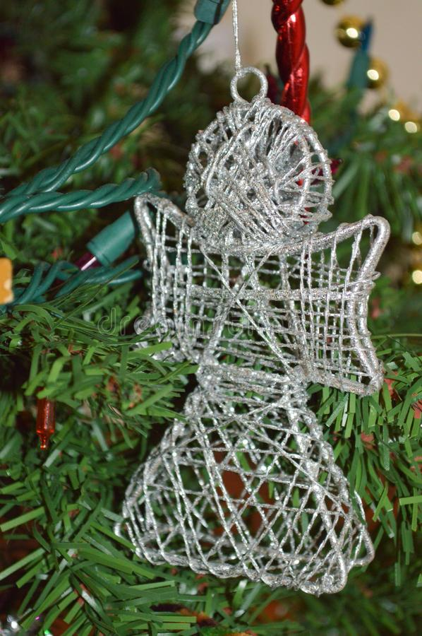 A close up photo of a plastic silver wire angel ornament with carolers at the bottom on a Christmas tree royalty free stock photos