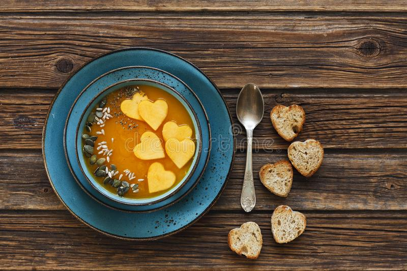 Close-up photo of the plate with fresh homemade pumpkin cream soup with seeds and heart shape toasts stock photo