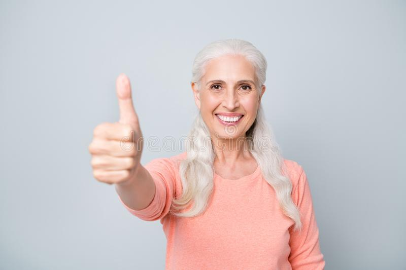 Close-up photo portrait of charming lady granny making finger up signal wearing peach color pullover  grey royalty free stock photography