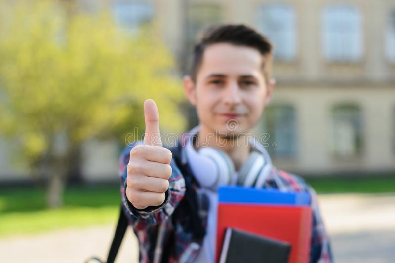 Close-up photo portrait of cheerful optimistic nice handsome cool self-assured guy holding copybooks in hands and making finger up. Signal royalty free stock photo