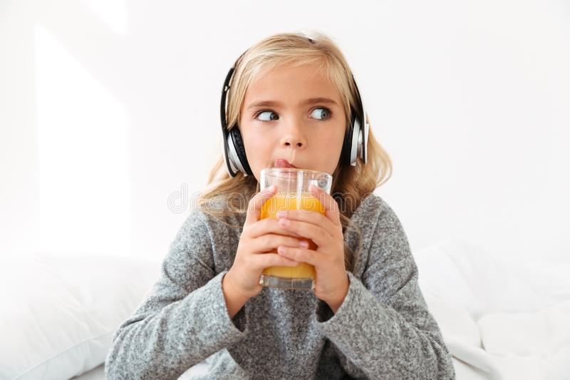 Close-up photo of pretty little girl in headphones licking while. Drinking orange juice, looking ae royalty free stock photos