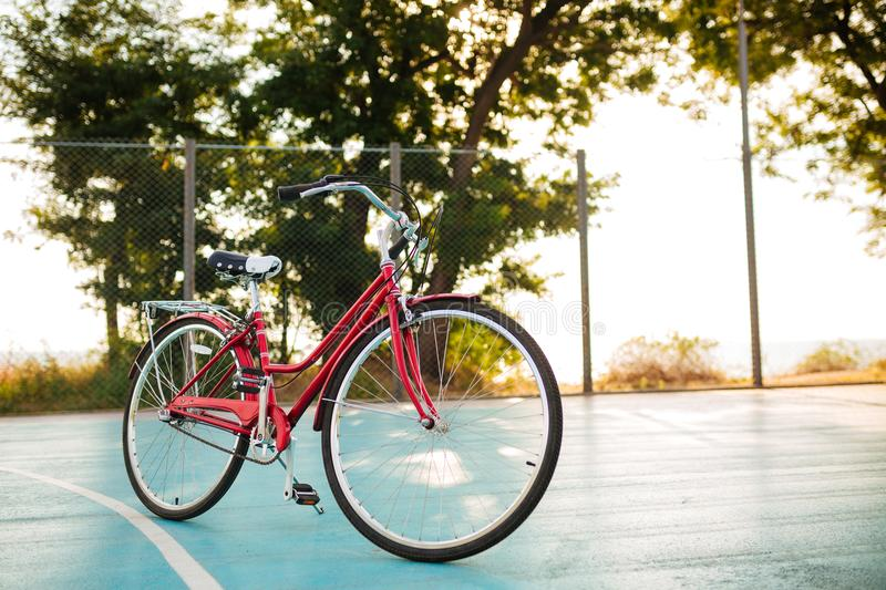 Close up photo of red classic bicycle standing on basketball court in park. Beautiful photo of bicycle royalty free stock image