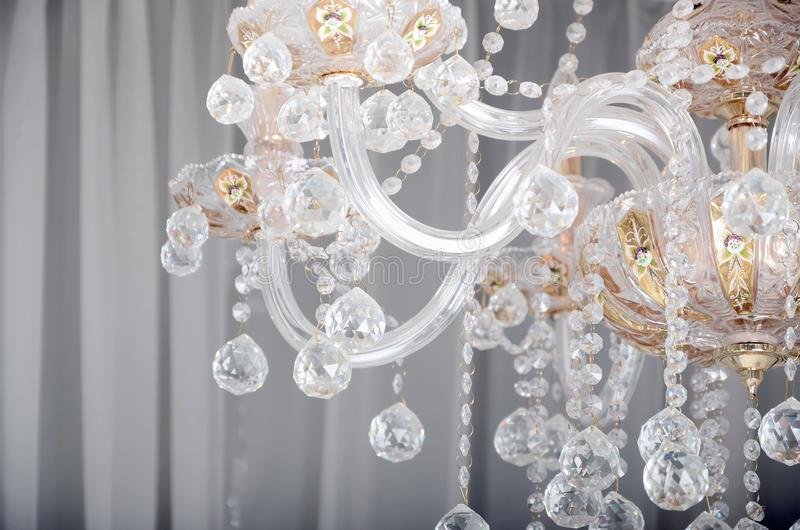 Close-up photo of the scenery on the old chandelier. Glass figures shine and reflect light with their faces royalty free stock image
