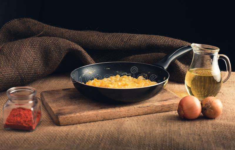 Close up photo of scrambled eggs with ground paprika, onions and oil - Rural style. Yellow scrambled eggs in black pan on wooden. Board stock images