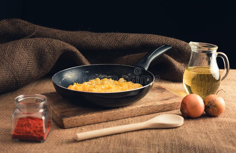 Close up photo of scrambled eggs with ground paprika, onions, oil and wooden ladle - Rural style. Yellow scrambled eggs in black. Pan on wooden board. n on royalty free stock images