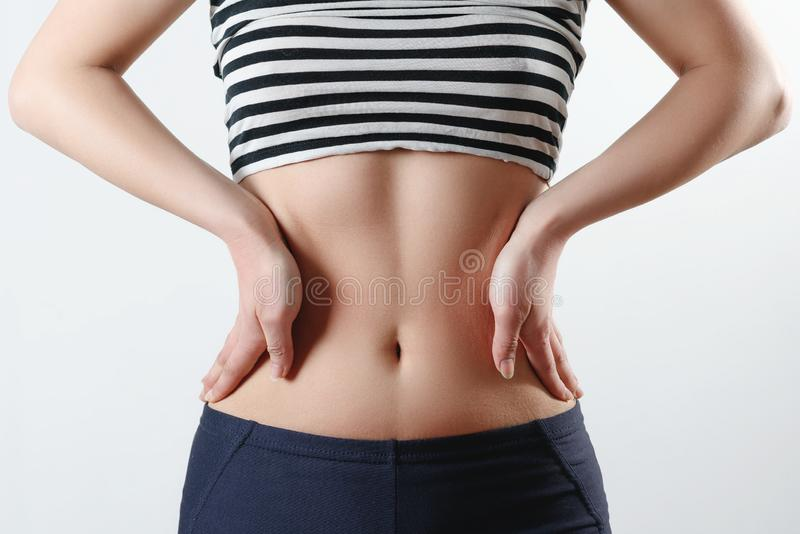 Close-up photo. a slender girl in sports leggings and a topic shows a tight figure and a tummy, holds her hands on the sides of royalty free stock photos