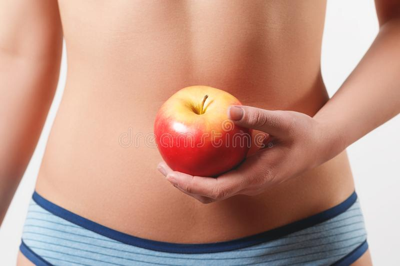 Close up. slender slim figure waist belly young woman girl. Holding a juicy red Apple. isolated on white background royalty free stock images