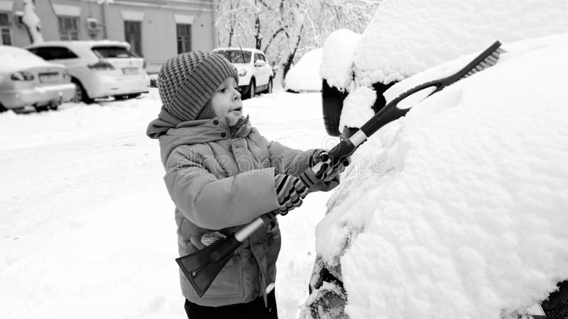 Close up photo of smiling happy cute boy in beige coat and hat , have fun to playing in the snow at the winter after royalty free stock image