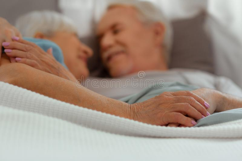 Close-up photo of spouses lying in the bed and hugging royalty free stock image