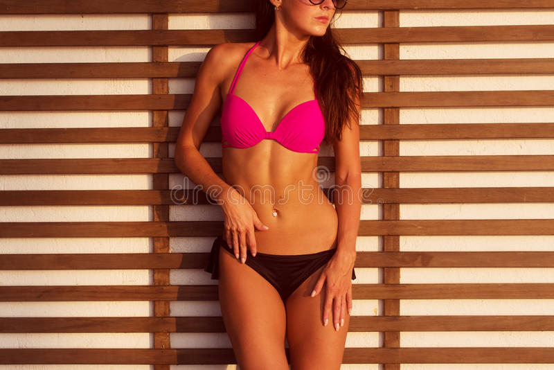 Close-up photo of tanned brunette model with body standing in bikini and sunglasses against wall wooden grating on. Close-up photo of tanned brunette model with stock photo