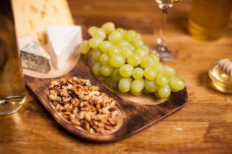 Close up photo of tasty walnuts on a cheese degustation next to fresh grapes. Honey jar. Bottle of white wine royalty free stock image