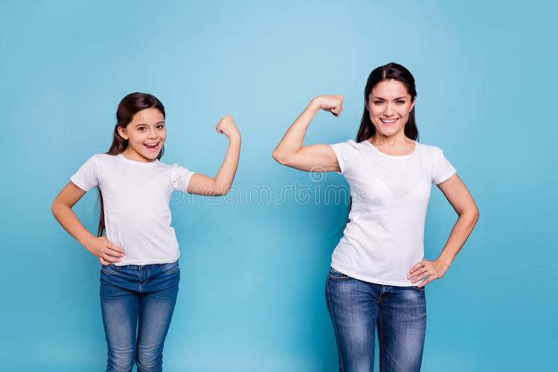 Close up photo two people brown haired mum mom small little daughter hand on biceps who run world girls wear white t. Shirts bright blue background stock photos