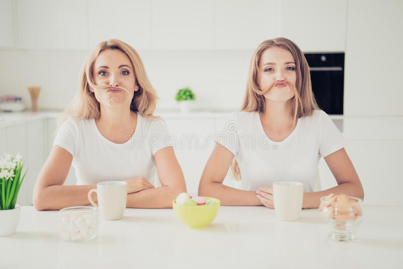 Close up photo two people mum teen daughter pretending man male guy making moustache with hair funny funky fooling royalty free stock images