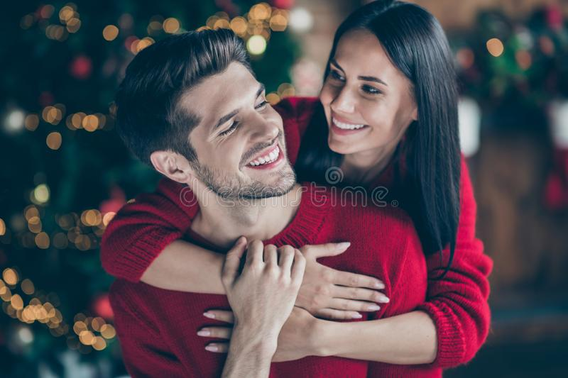 Close up photo of two people romantic dreamy man and woman hug gently piggyback in house with newyear decoration lights. Close up photo of two people romantic royalty free stock images