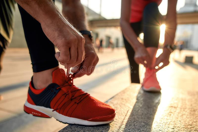Close up photo of two people in sport clothes tying shoelaces before jogging royalty free stock photos