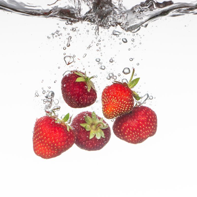 Close-up photo, on a very short exposure, strawberries falling into the water on a white background close up. Close-up photo, on a very short exposure royalty free stock images