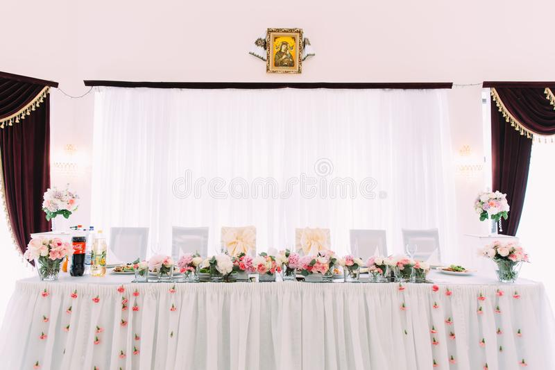 Close-up photo of the wedding table set decorated with pink flowers. Close-up photo of the wedding table set decorated with pink flowers stock photography