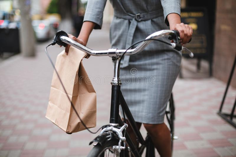 Close up photo of woman body in gray dress riding on bicycle along the street. Young lady riding bicycle with paper bag. Close up photo of woman body in gray royalty free stock photography