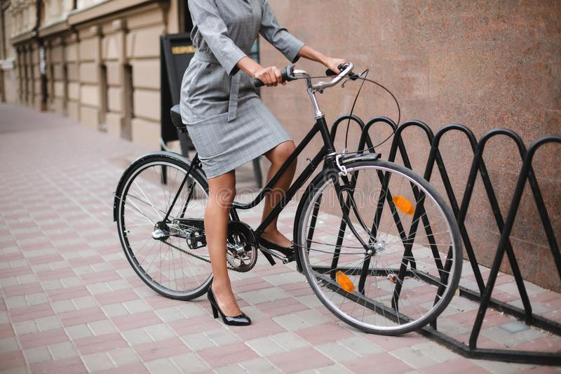 Close up photo of woman body in gray dress standing with bicycle. Young lady riding bicycle on street. Close up photo of woman body in gray dress standing with stock image